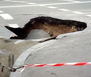 В Киеве двухметровая яма затянула в себя автомобиль